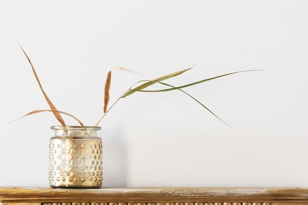 흰색 바탕에 오래 된 선반에 황금 항아리에 말린 된 식물 프리미엄 사진