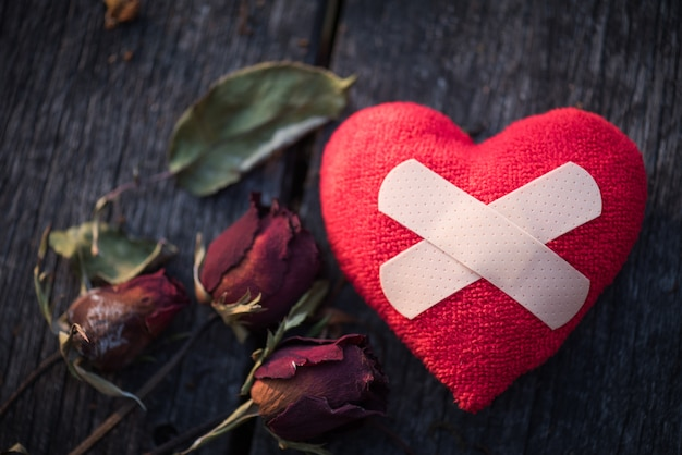 Dried red rose with red paper in shape of broken hearted on wooden background Premium Photo