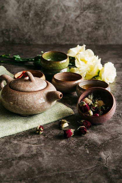 Dried rose flower with teapot; teacups and rose bouquet on concrete background Free Photo