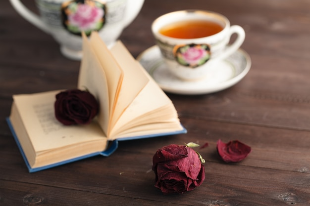 開いた本を置く乾燥したバラ Premium写真