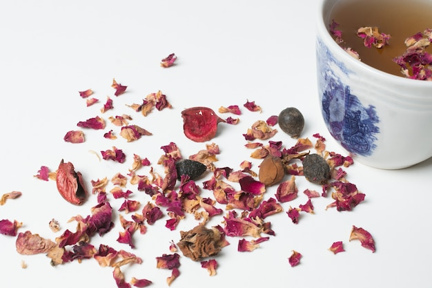 Dried rose petals and tea cup isolated on white background Free Photo