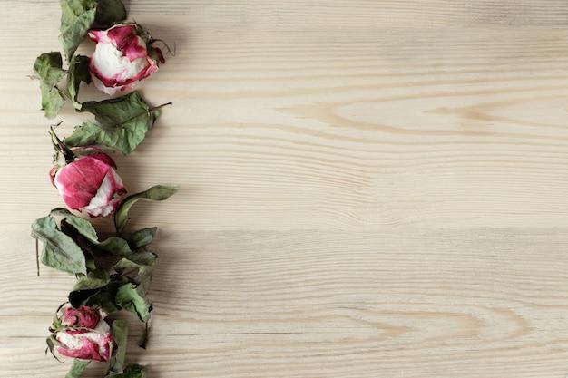 乾燥されたばらとコピースペース、トップビューで木製の背景の葉 Premium写真