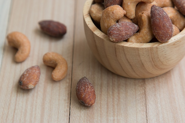 Dried salt cashew nuts and almond in a bowl on wooden table background Premium Photo