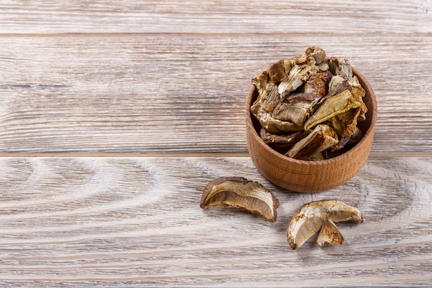 Dried shiitake mushroom in a bow , on a wooden table Premium Photo
