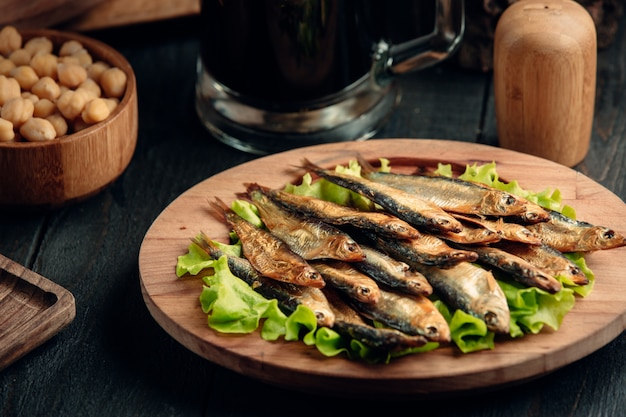 Dried smoked sprat layered on lettuce leaves served on round wood platter Free Photo