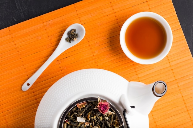 Dried tea herb and tea on place mat with ceramic teapot Free Photo