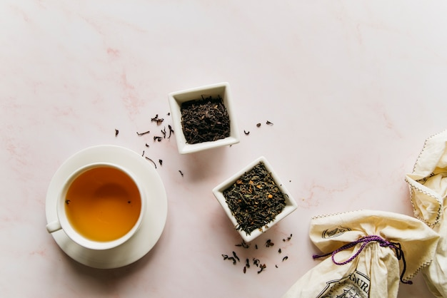 Dried tea herbs bowl with black tea on marble texture backdrop Free Photo