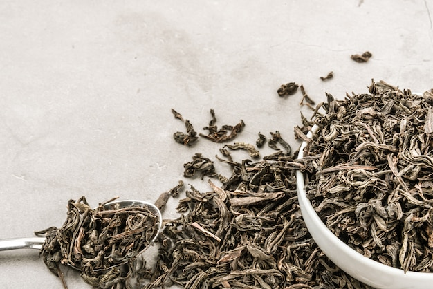 Dried tea in a white ceramic cup with a spoon on a gray textured Premium Photo