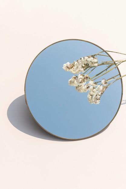 Fiore di statice bianco essiccato su uno specchio rotondo Foto Gratuite