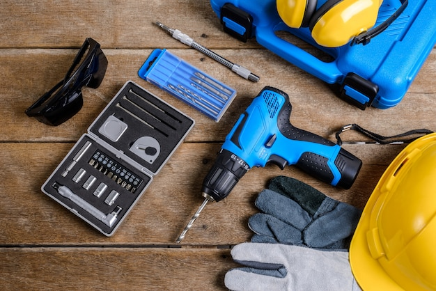 Drill and set of drill, tools, carpenter and safety, protection equipment Premium Photo