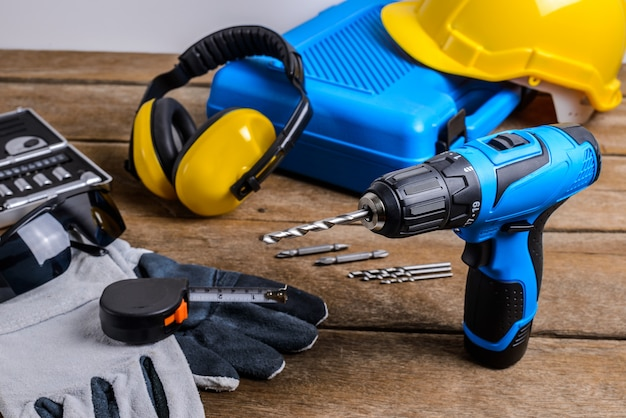Drill and set of drill,tools,carpenter and safety, protection equipment Premium Photo
