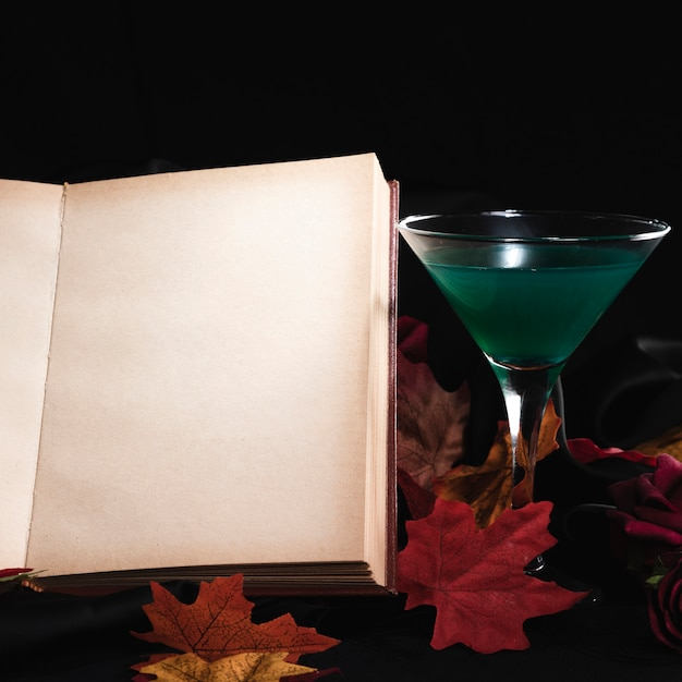 Drink with open book on black background Free Photo