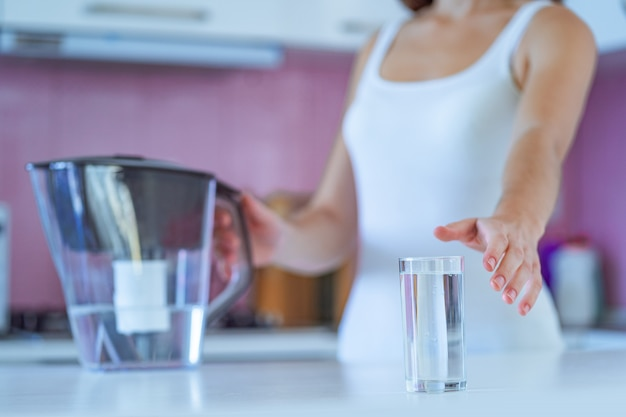 Drinking woman drinks clear purified water from a water filter in the morning in the kitchen at home Premium Photo