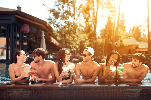 Drinks at poolside. happy friends enoying pool party. Premium Photo