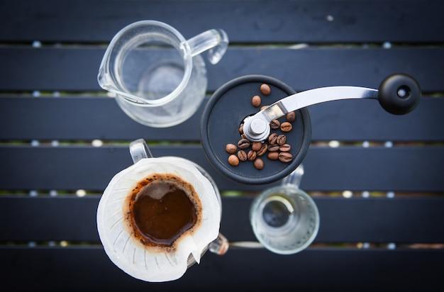 Капельный кофе бариста наливает воду на фильтрованное заваривание, делает чашку ручной капельного кофе Premium Фотографии