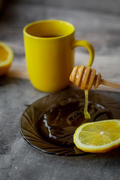 黄色いカップと灰色の受け皿に蜂蜜を滴下 Premium写真
