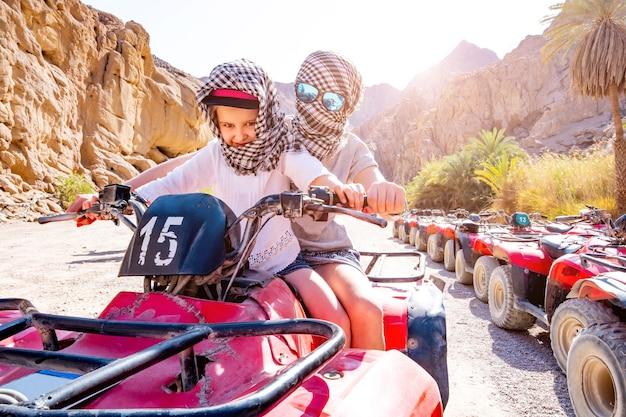 Водитель и ребенок на квадроцикле в сафари по пустыне Premium Фотографии