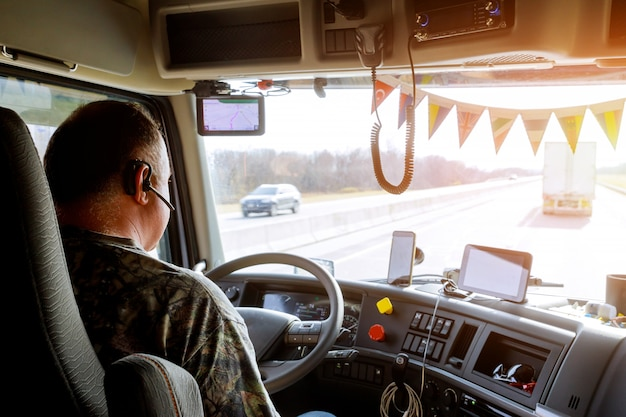 Driver in cabin of big modern truck Premium Photo