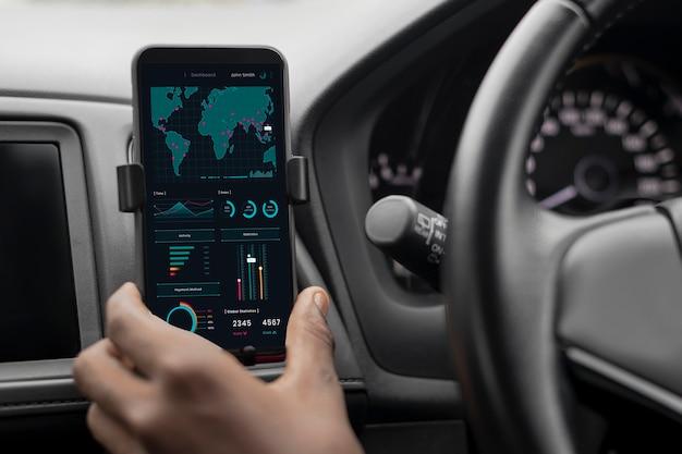 Водитель проверяет фондовый рынок по телефону в машине Бесплатные Фотографии