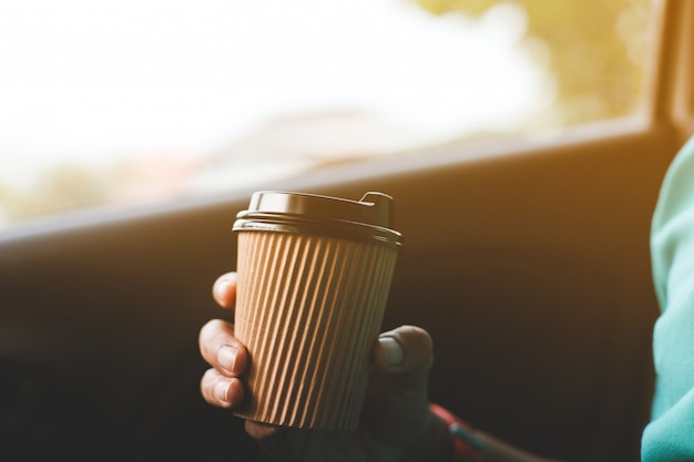 A driver drinking coffee in the car. Premium Photo