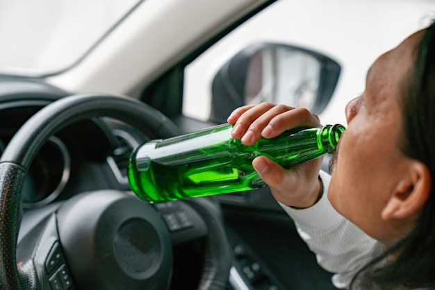 A driver holding alcoholic bottle while driving Premium Photo