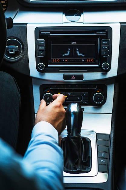 Driver's hand adjusting audio button in car Free Photo