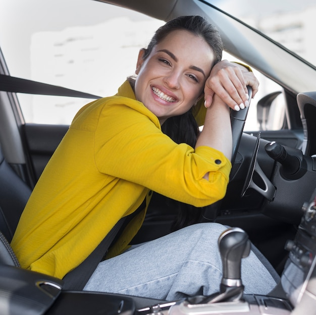 Driver smiles and leaning on the steering wheel Free Photo