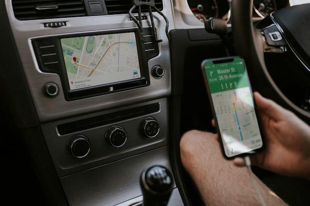 ナビゲーションに携帯電話を使用するドライバー 無料写真