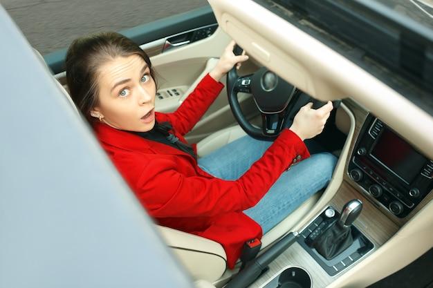 Езда по городу. молодая привлекательная женщина за рулем автомобиля Бесплатные Фотографии