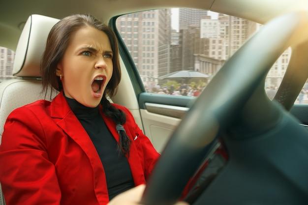 街中を運転。車を運転する若い魅力的な女性 無料写真