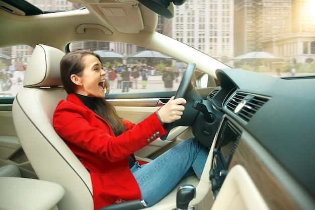 Guidare in città. giovane donna attraente alla guida di un'auto. giovane modello piuttosto caucasico in elegante giacca rossa alla moda che si siede all'interno del veicolo moderno. concetto di imprenditrice. Foto Gratuite