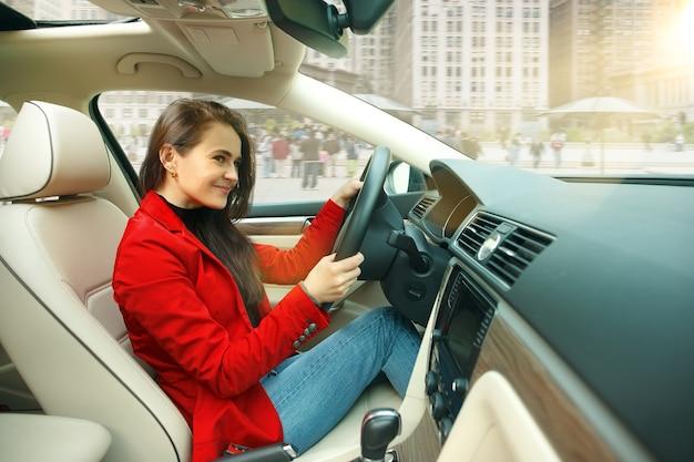 Guidare in città. giovane donna attraente alla guida di un'auto. giovane modello piuttosto caucasico in elegante giacca rossa alla moda che si siede all'interno del veicolo moderno. Foto Gratuite
