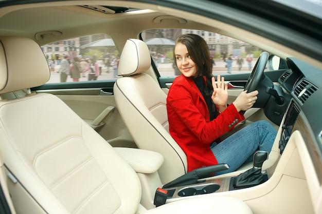 Guidare in città. giovane donna attraente alla guida di un'auto. giovane modello piuttosto caucasico in elegante giacca rossa alla moda che si siede all'interno del veicolo moderno Foto Gratuite