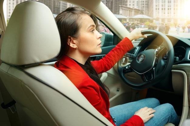 Guidare in città. giovane donna attraente alla guida di un'auto Foto Gratuite