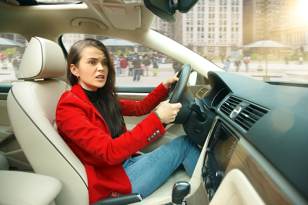 Guidare in città. giovane donna attraente alla guida di un'auto. Foto Gratuite