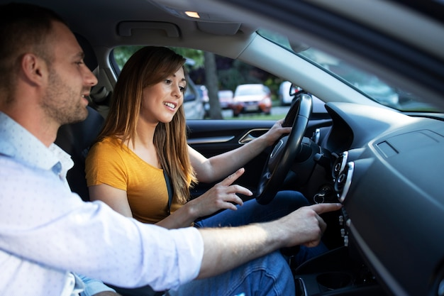 Driving instructor showing vehicle dashboard and buttons to the student taking driving lessons Free Photo