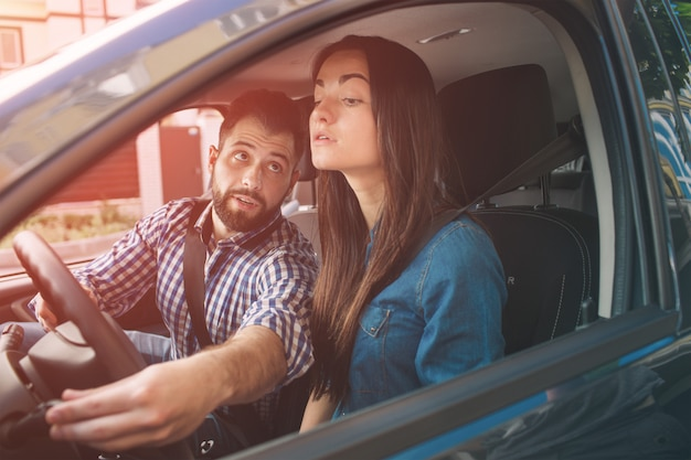 Driving test. young serious woman driving car feeling inexperienced, looking nervous at the road traffic for information to make appropriate decisions. man is an instructor, controlling and checking Premium Photo