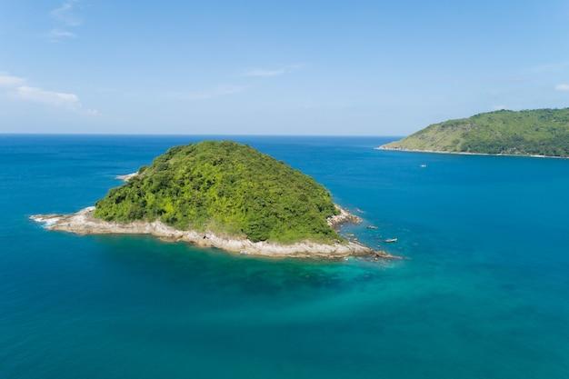 タイのプーケット島の海に美しい小さな島がある晴れた日の熱帯海のドローン空撮ショット。 Premium写真