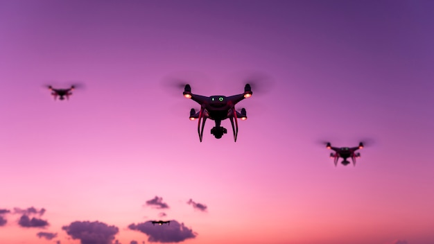 Drone quadcopter with digital camera flying in sunset evening time beautiful light Premium Photo