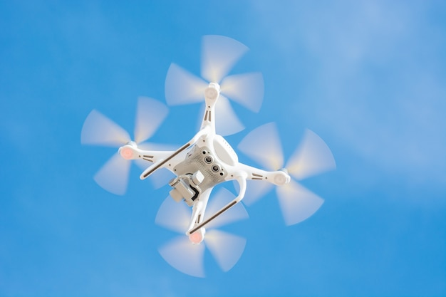 Drone of white color flying in the blue sky, concept video technology. Premium Photo