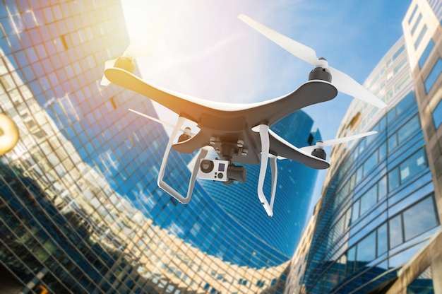 Drone with digital camera flying in a modern city at sunset Premium Photo