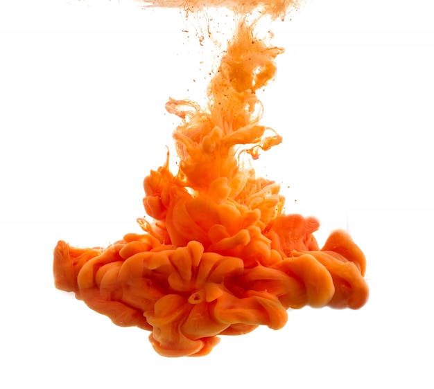 Drop of orange paint falling in water Free Photo