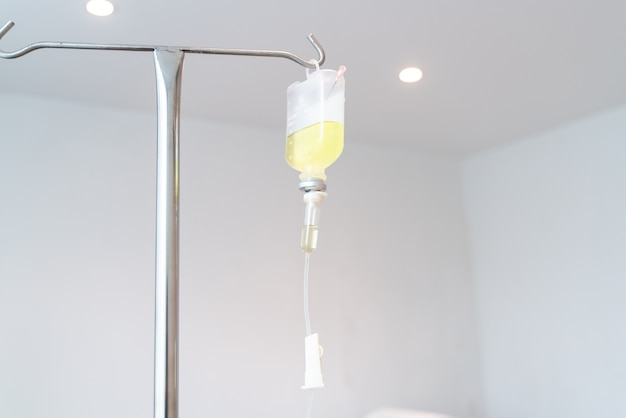 Drop of saline solution,iv drip chamber, iv tubing hanging on a metal pole in the room Premium Photo