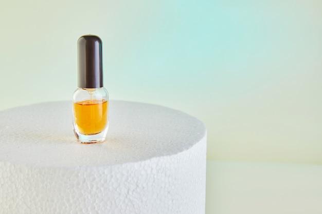 スポイトボトル-白い表彰台のラベルのない香水瓶用の琥珀色のガラス Premium写真