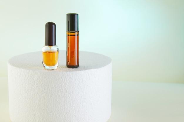 スポイトボトル-香水の琥珀色のガラス、シャワージェル、白い表彰台にラベルのないボトル。 Premium写真