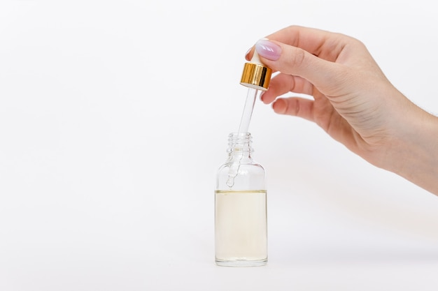 Dropper glass bottle mock-up. oily drop falls from cosmetic pipette on white background Premium Photo
