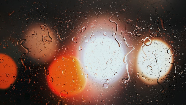 Drops of rain flow down the glass against the bokeh background of moving cars Premium Photo