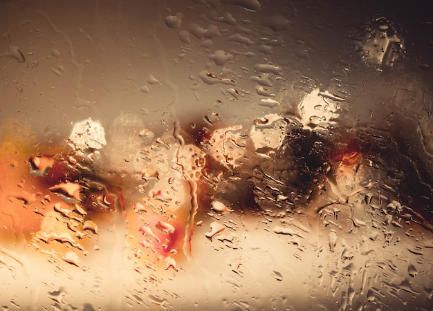 Drops of rain wiht street bokeh lights out of focus autumn abstract backdrop Premium Photo