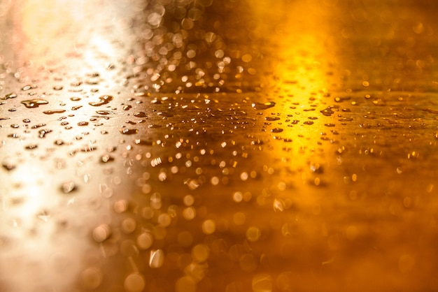 Drops of rain on a wooden table illuminated by streetlights one night. Premium Photo