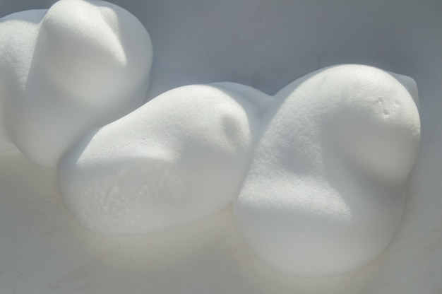 Drops of shaving foam, mousse or hair styling foam on white background Premium Photo